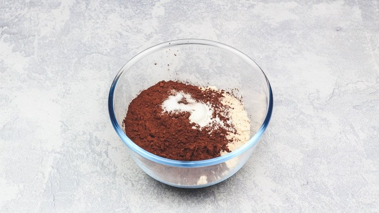 Flour, cocoa powder, baking powder, and salt in bowl ready to be whisked.