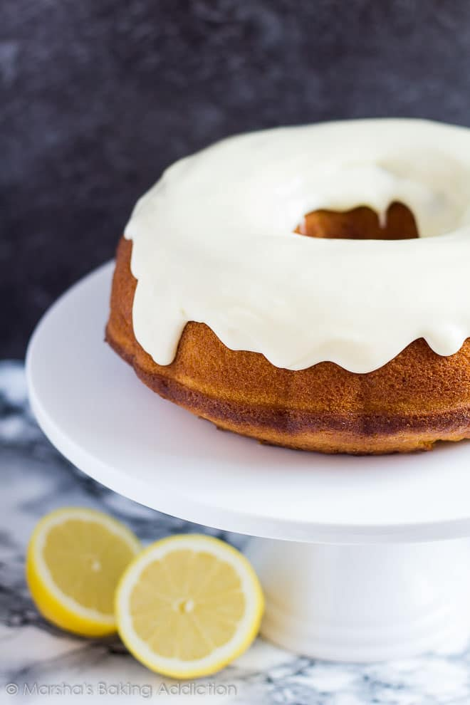 Lemon Bundt Cake topped with a thick icing served on a white cake stand.