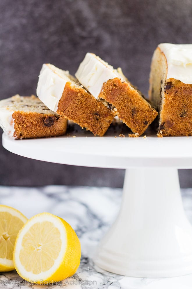 Chocolate Chip Lemon Bread served on a white cake stand with three slices cut off.