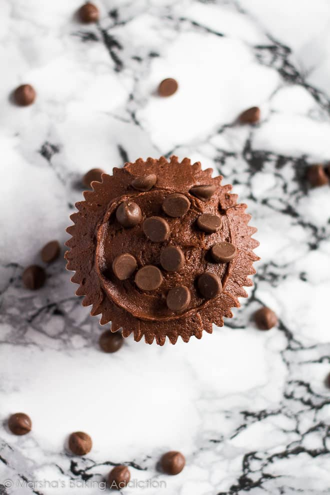 Overhead shot of a frosted Double Chocolate Cupcake topped with chocolate chips on a marble background.