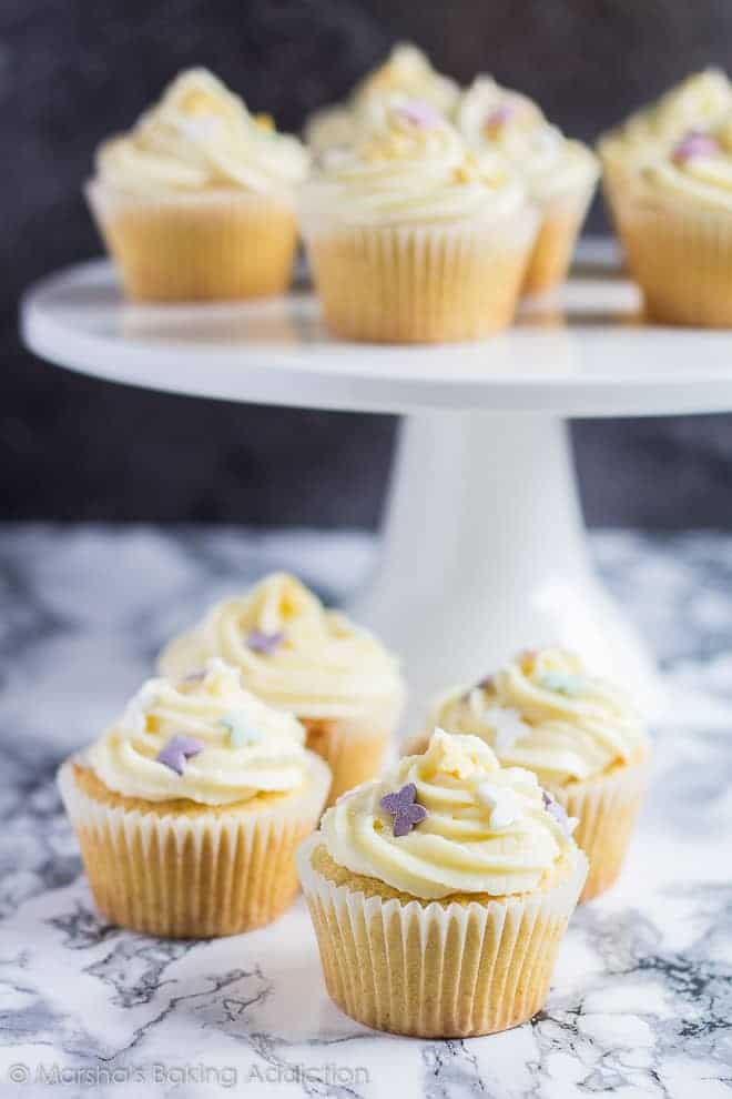 Perfect Vanilla Cupcakesserved on a white cake stand and on marble background.