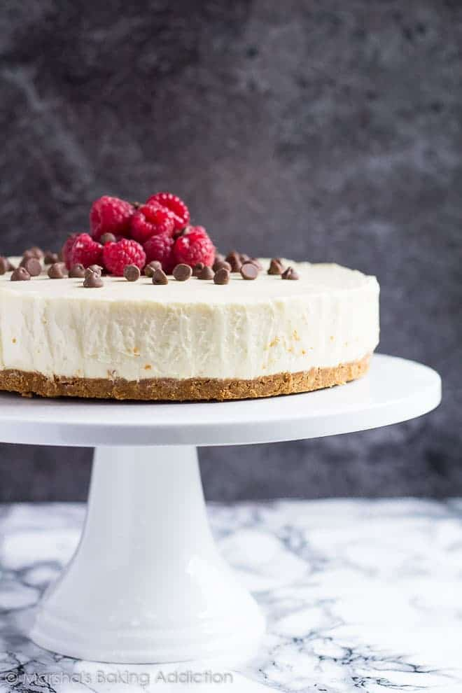 White Chocolate Torte topped with chocolate chips and raspberries served on a white cake stand.