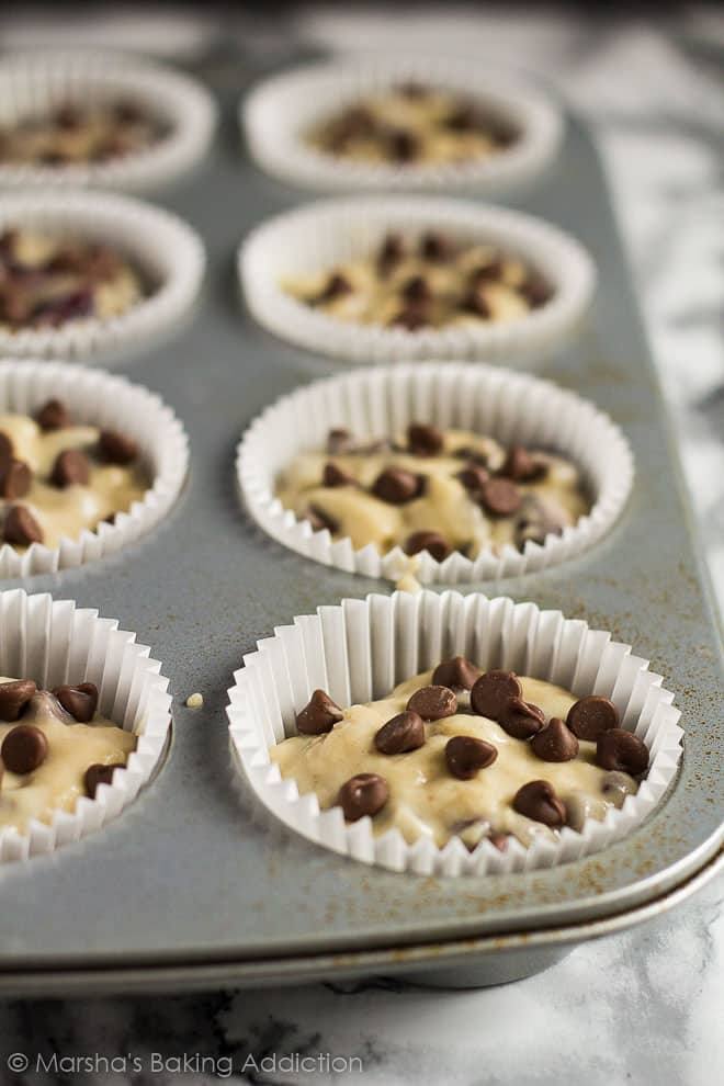 Chocolate Chip Cherry Muffin batter in muffin cases in a muffin pan.