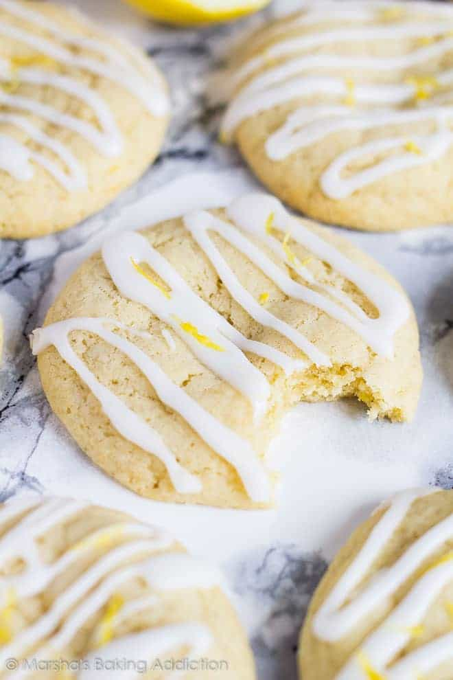 Soft and Chewy Lemon Cream Cheese Cookies drizzled with a glaze with a bite taken out of one cookie.
