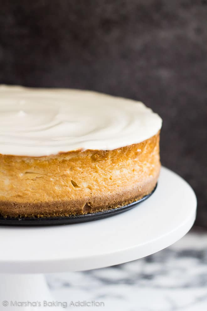 Perfect Vanilla Cheesecaketopped with a sour cream topping served on a white cake stand.