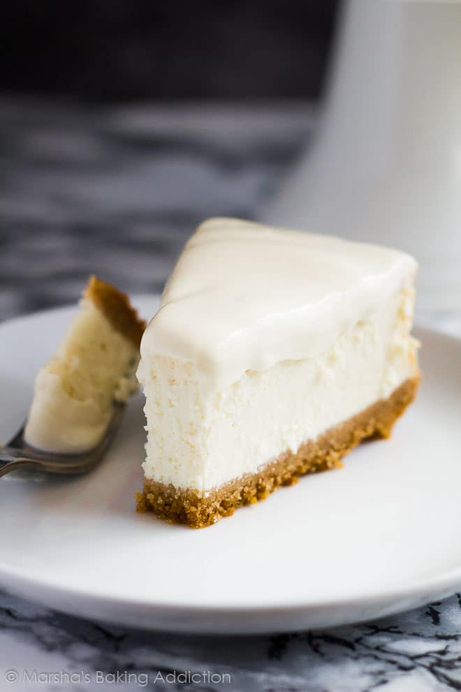 Perfect Vanilla Cheesecake slice with a sour cream topping served on a white plate with a fork.