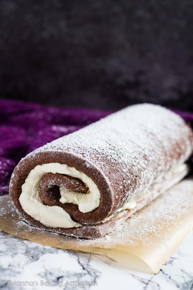 Chocolate Swiss Rolldusted with icing sugar on brown parchment paper.