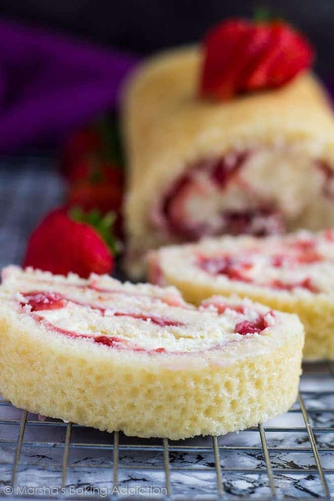 Strawberries and Cream Swiss Roll cut into slices on a wire rack.