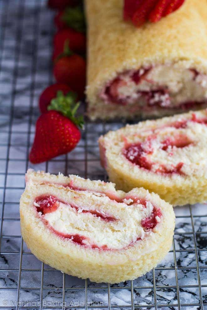 Overhead shot of Strawberries and Cream Swiss Roll slices on a wire rack.