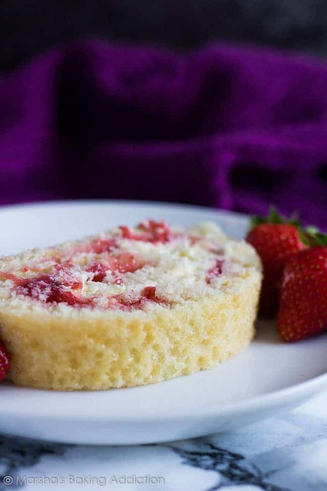 A slice of Strawberries and Cream Swiss Roll served on a white plate with whole strawberries.