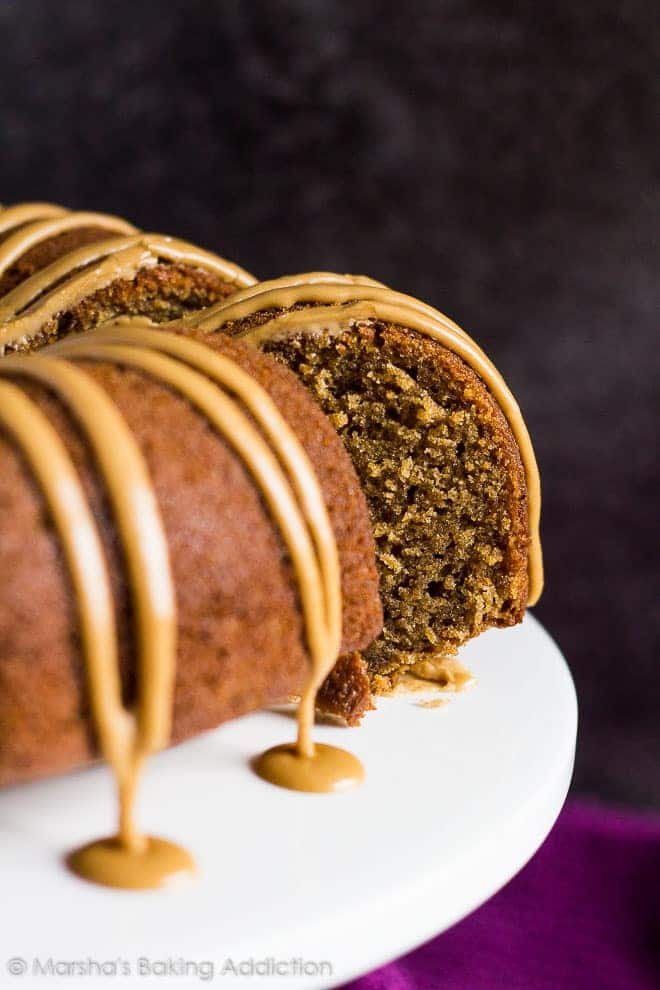 A glazed Coffee Bundt Cake on a white cake stand with a slice cut out.