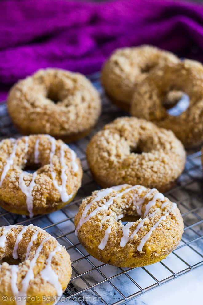 Baked Pumpkin Streusel Doughnutsdrizzled with a glaze on a wire rack.