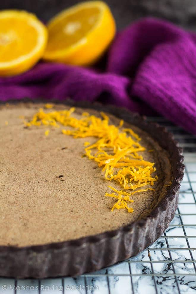 Close-up of Dark Chocolate Orange Tart topped with orange zest on a wire rack.