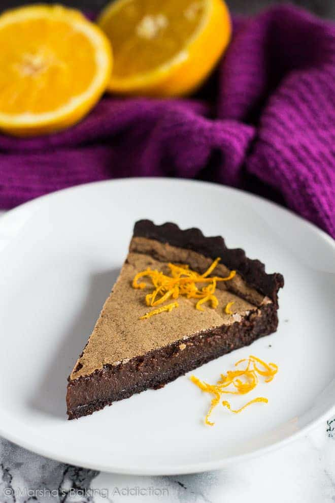 A slice of Dark Chocolate Orange Tart topped with orange zest served on a white plate.