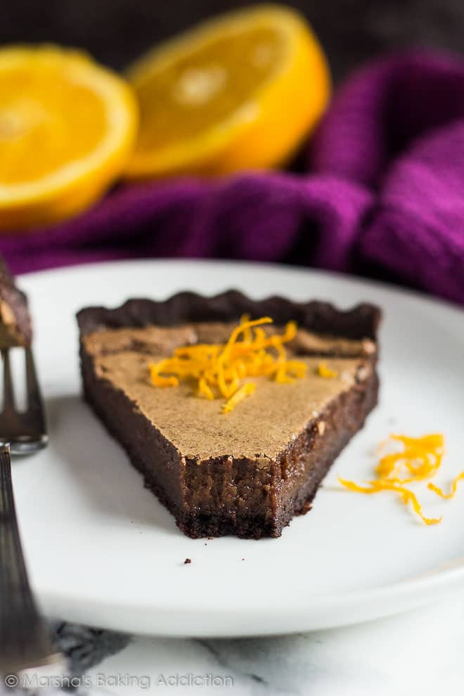 A slice of Dark Chocolate Orange Tart topped with orange zest served on a white plate with a fork.