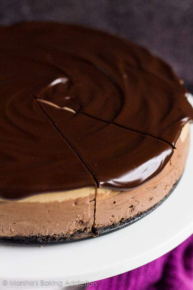 Layered Mocha Cheesecake topped with shiny chocolate ganache with a slice cut out on a white cake stand.