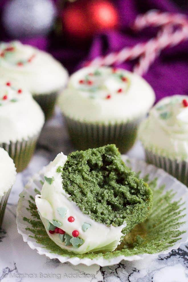 A cream cheese frosted green velvet cupcake on its side on the wrapper with a bite taken out of it.