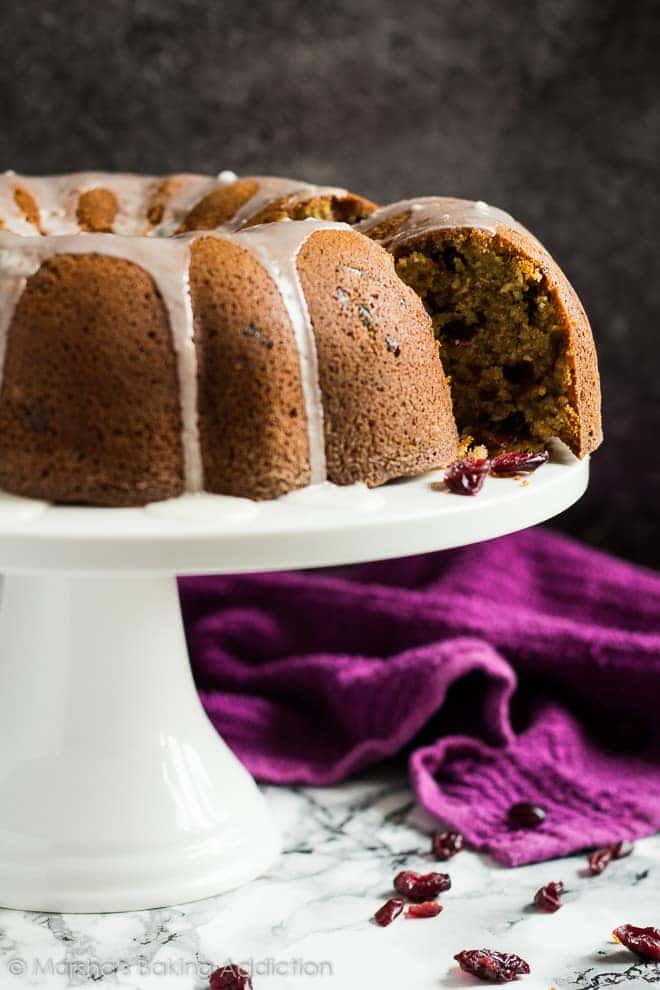 Glazed cranberry orange bundt cake with a cut out slice coming out of the side on white cake stand.