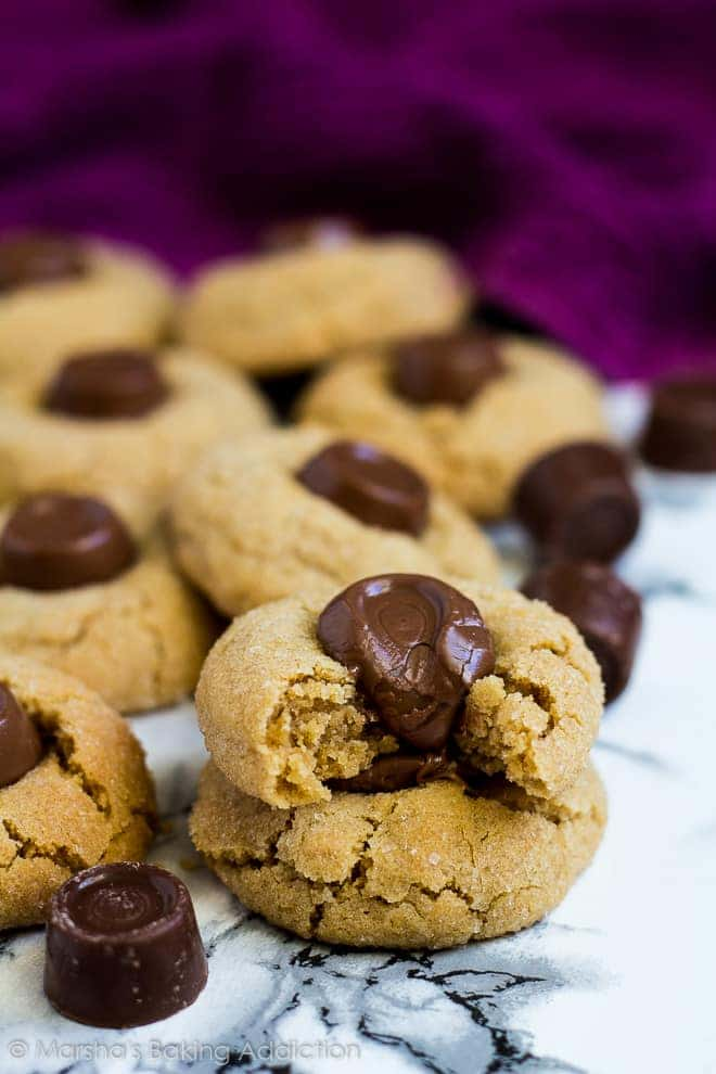 A stack of two Rolo peanut butter blossom cookies with a bite taken out of the top cookie on marble background.