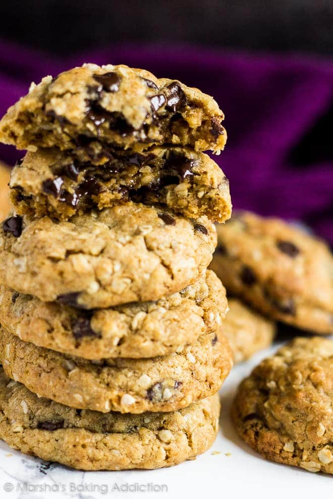Tall stack of healthier chocolate chip cookies with top cookie broke in half to show off melting chocolate chips.