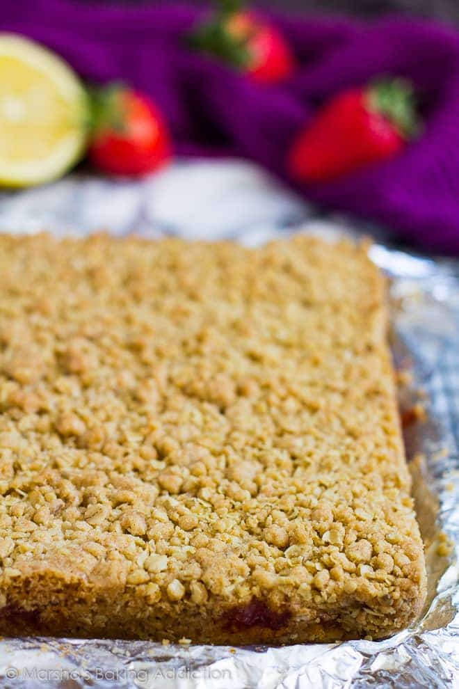 Strawberry lemon crumb bars in foil before being sliced with strawberries and lemon in background.