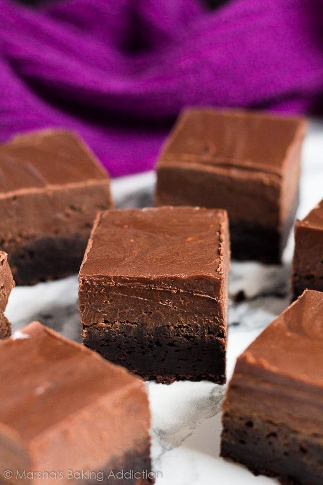 Thick brownies topped with a layer of thick, creamy Nutella fudge on marble background.