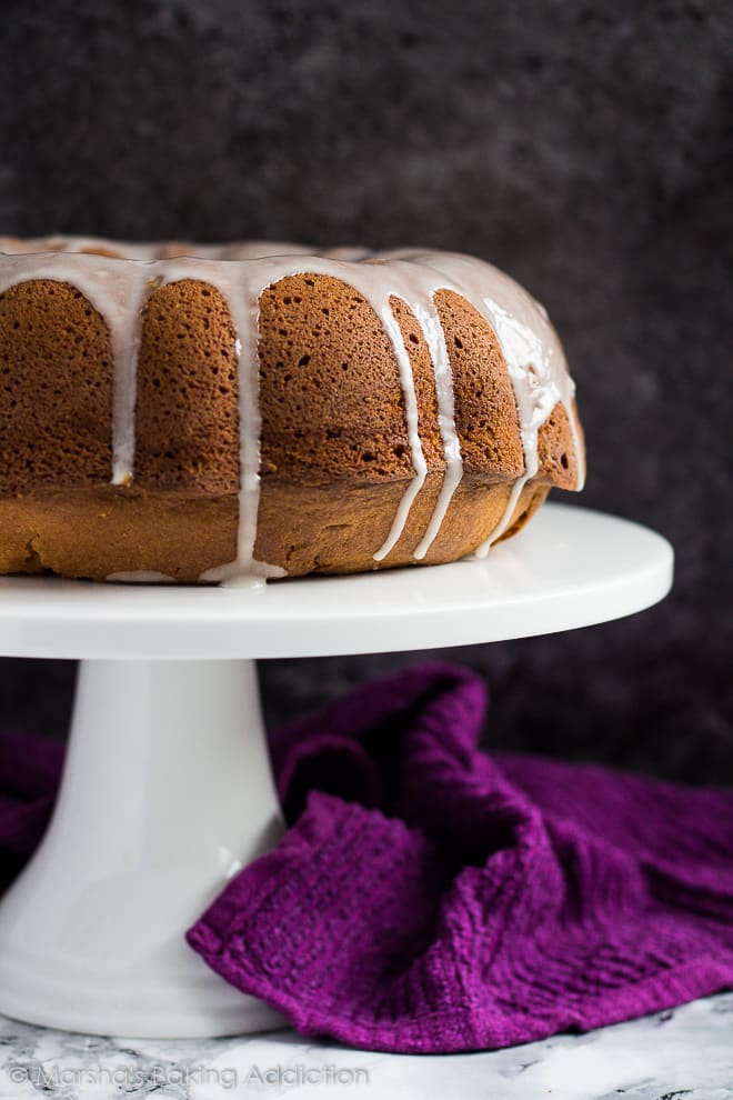 Glazed peanut butter and jam bundt cake on white cake stand.