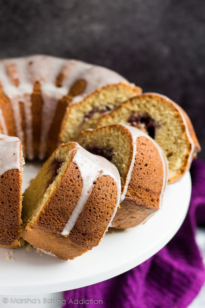 Glazed peanut butter bundt cake with three slices overlapped on white cake stand to show jam filling.