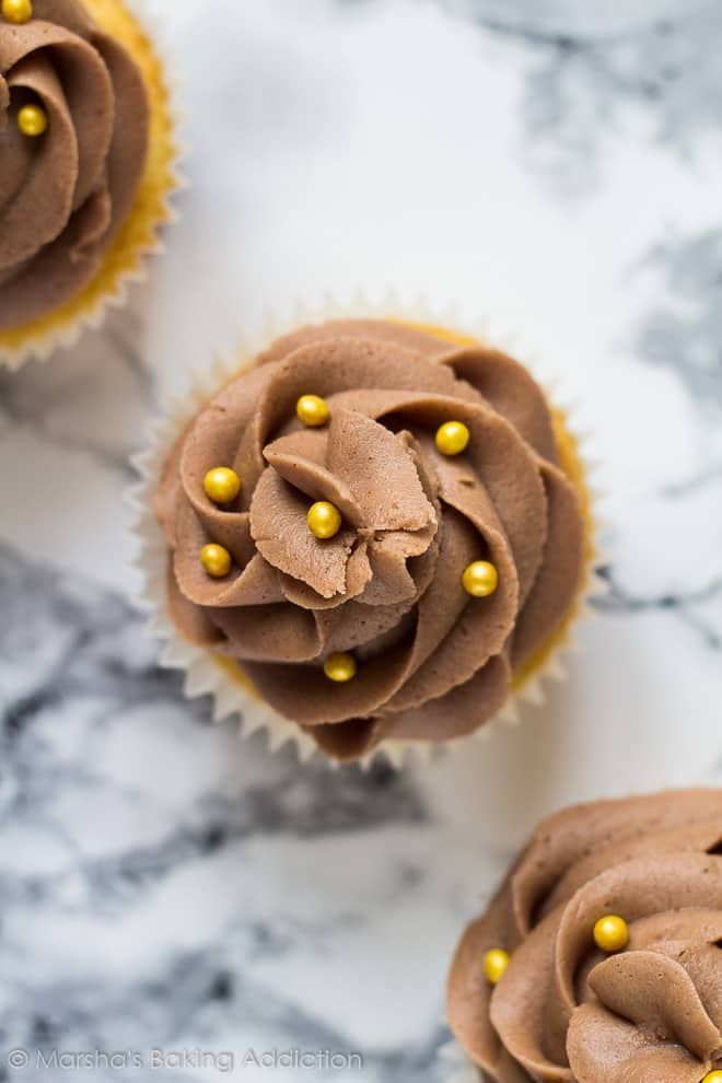 Overhead shot of three yellow cupcakes in a row with chocolate buttercream and gold ball sprinkles.