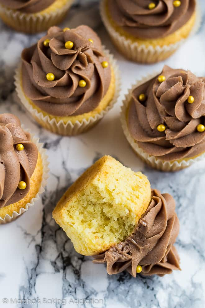 Overhead shot of chocolate buttercream frosted yellow cupcakes with one on its side with a bite taken out of it.