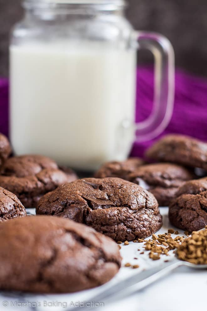 Side-view of thick chocolate chip mocha cookies with a mason jar of milk in background.