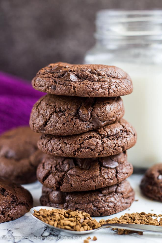 A tall stack of chocolate chip mocha cookies with a mason jar of milk in background.