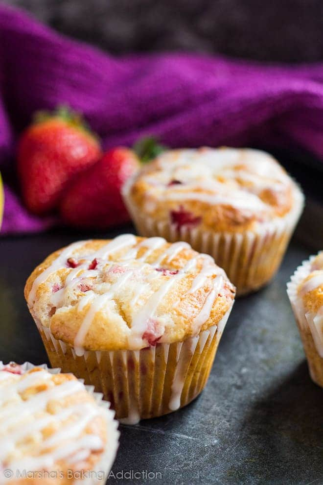 Strawberry lemon muffins drizzled with a sweet glaze on a baking tray.