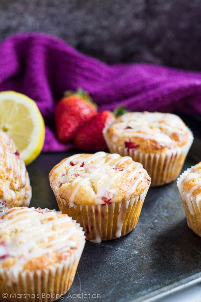 Strawberry lemon muffins drizzled with a glaze on a baking tray with strawberries in background.