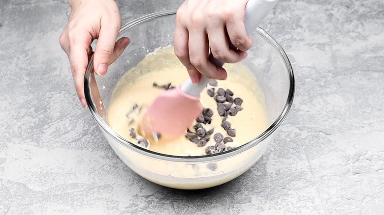 Adding chocolate chips to pancake batter in bowl.