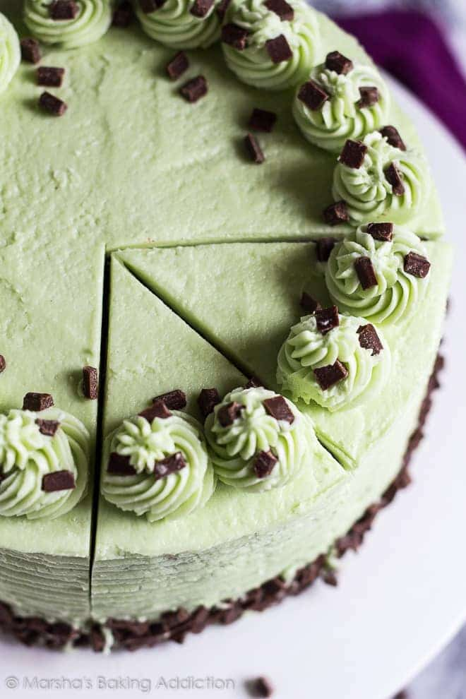 Overhead shot of mint chocolate chip layer cake with two slices cut out on white cake stand.