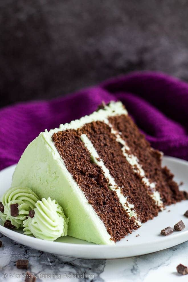 A slice of mint chocolate chip layer cake served on a small white plate.