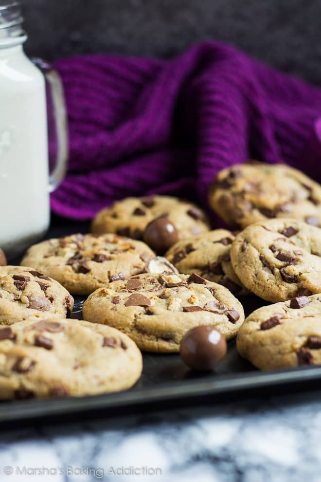 Chocolate chip cookies with Maltesers and a mason jar of milk on a baking tray.