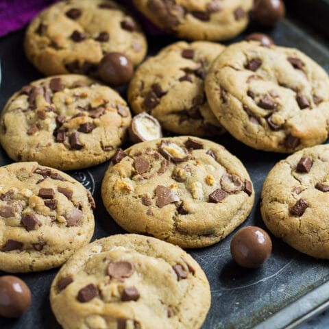 Overhead shot of chocolate chip cookies with Maltesers on a baking tray.