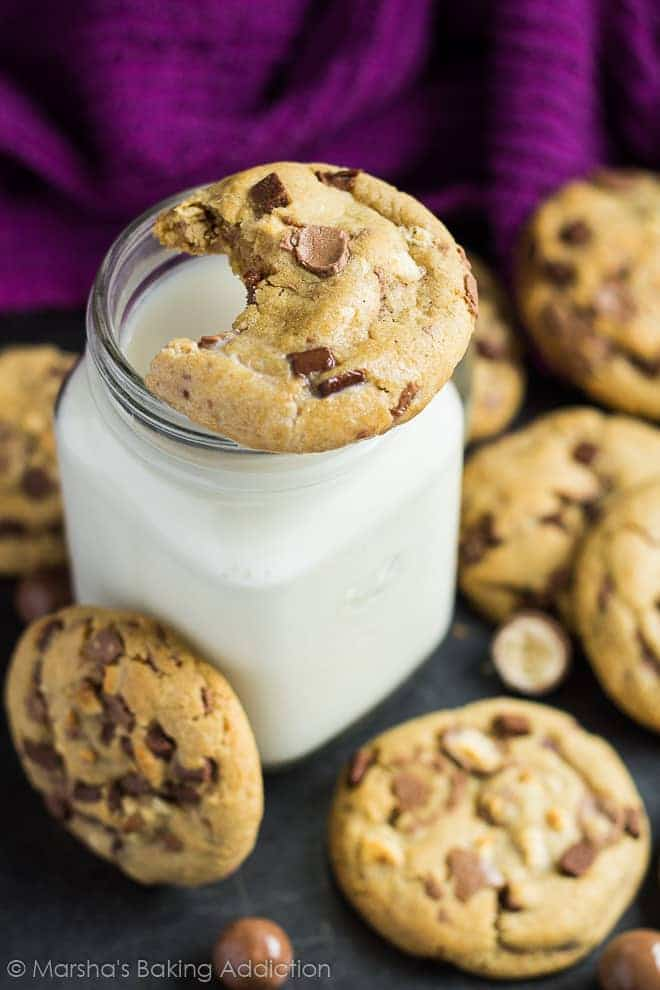 A bitten malted chocolate chip cookie resting a a mason jar of milk on a baking tray.