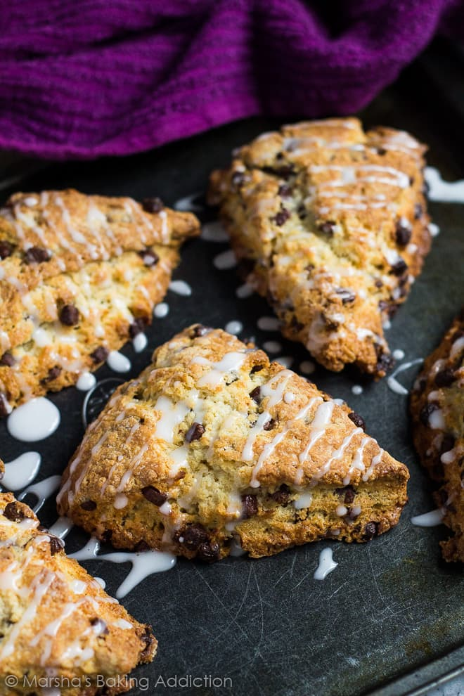 Chocolate chip scones drizzled with a glaze on a baking tray.