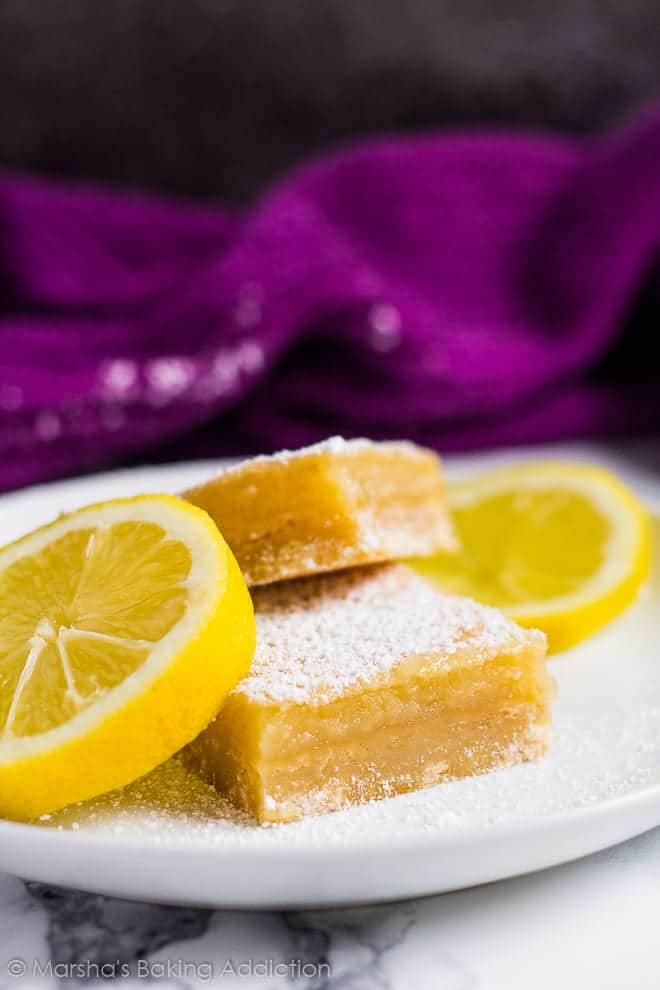 Two thick lemon bars dusted with icing sugar served overlapped on a small white plate with lemon slices.