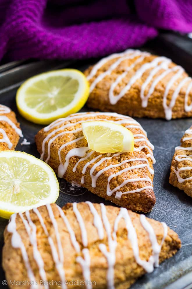 Lemon scones drizzled with a lemon glaze with lemon slices on a baking tray.