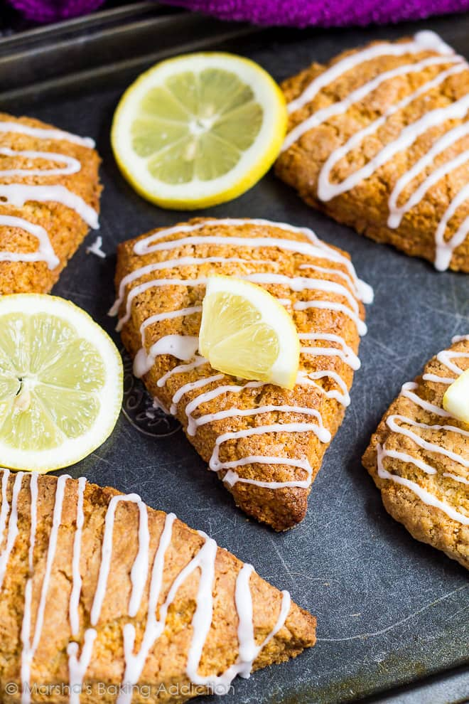 Overhead shot of lemon scones drizzled with a glaze with lemon slices on a baking tray.