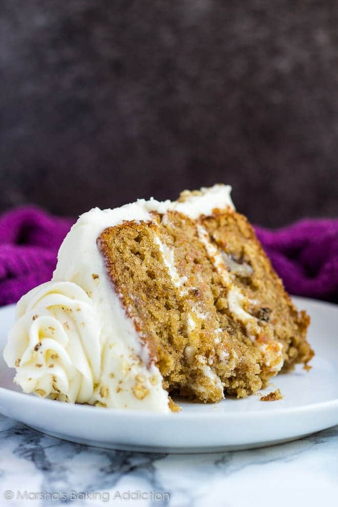 A thick slice of cream cheese frosted carrot layer cake served on a small white plate.