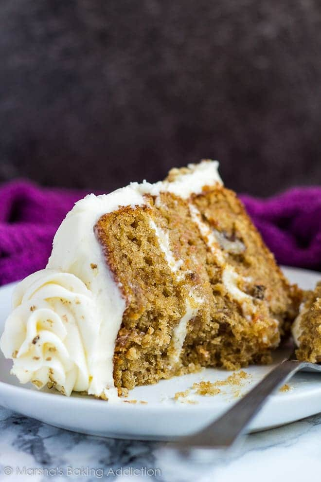 A thick slice of carrot layer cake with cream cheese frosting served on a small white plate with a fork.