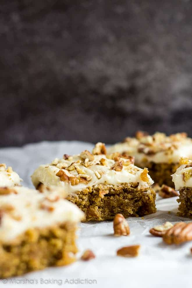 Cream cheese frosted carrot cake blondies topped with chopped pecans on parchment paper.