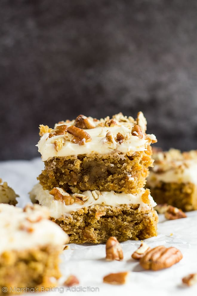 Two stacked cream cheese frosted carrot cake blondies topped with chopped pecans on parchment paper.