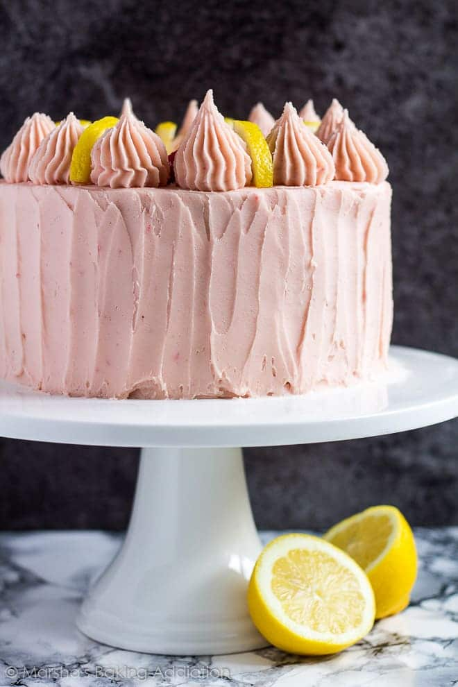 A pink lemon raspberry layer cake topped with piped swirls and lemon slices on a white cake stand.