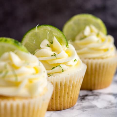 A row of three frosted Margarita cupcakes with lime slices.